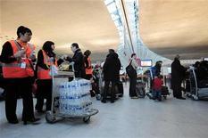<p>Des salariés d'Aéroports de Paris (ADP) à l'aéroport Charles-de-Gaulle, à Roissy. Aéroports de Paris a annoncé lundi son entrée au capital de l'opérateur aéroportuaire turc TAV Havalimanlari Holding, dont il va prendre 38% pour 874 millions de dollars (670 millions d'euros environ), confirmant ce qu'avaient dit la veille à Reuters des sources proches de la transaction. /Photo d'archives/REUTERS/Julien Muguet</p>
