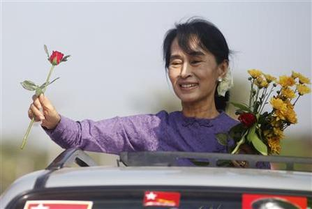 Myanmar's pro-democracy leader Aung San Suu Kyi holds flowers given by supporters as she stands on a vehicle en-route to Kawhmu township, the constituency where she will contest April by-elections, in this February 11, 2012 file photo. After decades of military dictatorship, a nominally civilian government last year embarked on a series of dramatic reforms. It has released political prisoners, including Suu Kyi, relaxed media controls and vowed to tackle its dysfunctional economy. But the United States and European Union regard free and fair by-elections as a crucial condition for dismantling years of economic and political sanctions against Myanmar. REUTERS/Soe Zeya Tun/Files