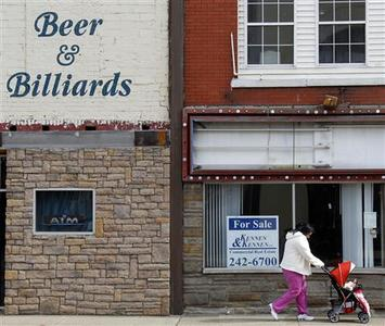 A woman pushes a baby carriage past a bar and one of many empty storefronts in Wheeling, West Virginia March 6, 2012. The economically depressed city is emblematic of the regional conditions and could get a big boost from a new chemical plant planned for the area. REUTERS/Jason Cohn