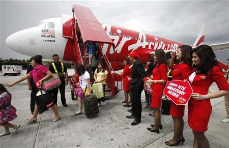 AirAsia staff greet passengers arriving from Kota Kinabalu to the Low Cost Carrier Terminal in Sepang outside Kuala Lumpur December 8, 2011. REUTERS/Bazuki Muhammad