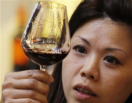 A visitor checks a wine in this file photo at Vinexpo Asia-Pacific held at the Hong Kong Convention and Exhibition Centre May 25, 2010.  REUTERS/Bobby Yip