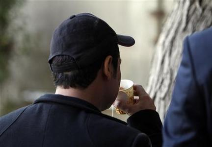 A man who goes by the name Haifa drinks tea with his back to the camera so as not to be identified in Baghdad March 12, 2012. REUTERS/Saad Shalash