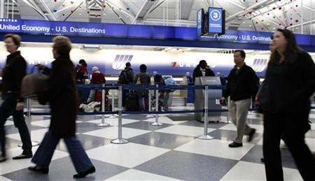 Passengers walk through terminal 1 while others wait at the United Airlines ticket counter at O'Hare International airport in Chicago November 24, 2010. REUTERS/Frank Polich
