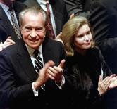 Former US President Richard Nixon and his daughter Tricia Nixon Cox applaud during a memorial service in New York December 29