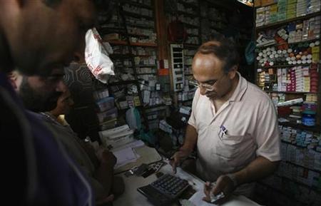 Customers buy medicine from a chemist (R) in Srinagar August 29, 2008. REUTERS/Fayaz Kabli/Files