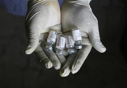 A worker displays bottles of a vaccine during a vaccination programme on the outskirts of Siliguri August 5, 2008. REUTERS/Rupak De Chowdhuri/Files
