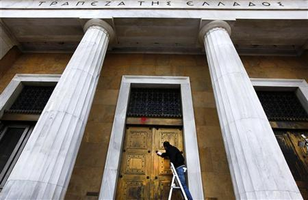 A worker cleans paint thrown by anti-austerity protesters at the facade of the Bank of Greece in central Athens March 6, 2012. REUTERS/Yannis Behrakis