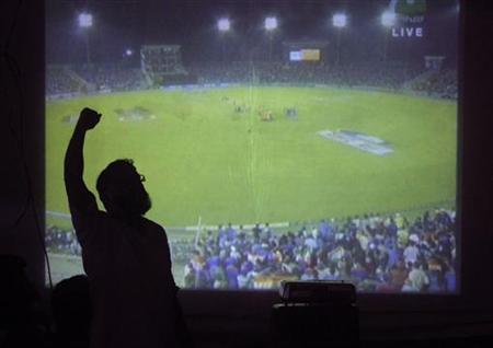 A cricket fan celebrates in support of Pakistan while watching their match against India from a projector along a roadside in Karachi on March 30, 2011. REUTERS/Athar Hussain