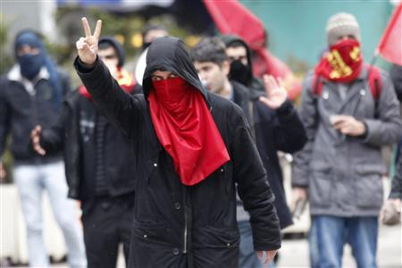 A protester makes a v-sign as he and others clash with Turkish police as they protest against the dropping of a case against five people charged with killing 37 writers and liberals in a 1993 hotel fire set off by Islamist rioters in Ankara March 13, 2012. REUTERS/Umit Bektas