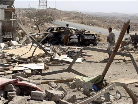 People inspect the scene of a suicide car bomb attack at a checkpoint outside the Yemeni city of al-Bayda March 13, 2012. REUTERS/Stringer