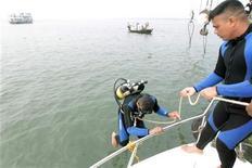 Спасатели работают на реке Менгха, где затонул паром, в 50 километрах к югу от Дакки 13 марта 2012 года. Пассажирский паром с 250 пассажирами на борту затонул в реке на юге Бангладеш во вторник после столкновения с баржей - по меньшей мере 35 человек погибли, сообщили местная полиция и очевидцы событий. REUTERS/Andrew Biraj