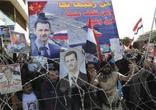 Живущие в Ливане сирийцы на демонстрации в поддержку президента Сирии Башара аль-Асада в Бейруте 4 марта 2012 года. Президент Сирии Башар аль- Асад, уже год борющийся с масштабными антиправительственными протестами, назначил парламентские выборы на 7 мая, сообщил сирийский парламент на своем официальном сайте. REUTERS/Hussam Shbaro