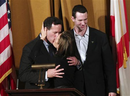U.S. Republican presidential candidate Rick Santorum receives a kiss from his wife Karen (R) while son John looks on, after speaking at the Alabama Republicans forum at the Alabama Theater in Birmingham, Alabama March 12, 2012. REUTERS/Marvin Gentry