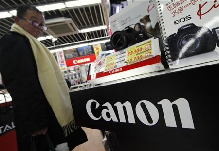 A man looks at Canon products displayed at an electronics store in Tokyo January 30, 2012. REUTERS/Toru Hanai