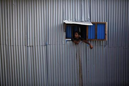 A man looks out of a window from a shanty in Dharavi, one of Asia's largest slums, in Mumbai September 28, 2010. REUTERS/Danish Siddiqui/Files