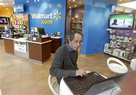 A customer, seen through a store window, sits at a laptop computer at a Wal-Mart.com store at the Topanga Plaza in Canoga Park, California, November 8, 2011. REUTERS/Fred Prouser