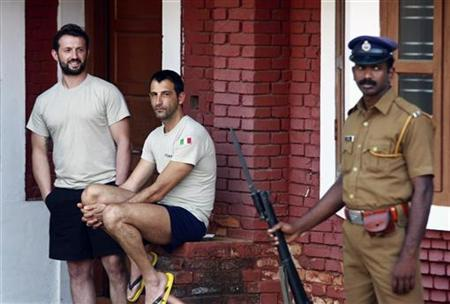 Salvatore Girone (L) and Latorre Massimiliano, members of the navy security team of Italian merchant vessel Enrica Lexie, are seen at the lawns of a guest house of the Central Indian Security Force, as a policeman (R) stands guard in Kochi February 26, 2012. REUTERS/Sivaram V