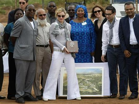 Pop star Madonna lays the first stone during a bricklaying ceremony at the site of her Raising Malawi Girls Academy, near the capital Lilongwe, April 6, 2010. REUTERS/Mike Hutchings