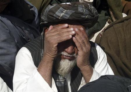 An Afghan man reacts during a ceremony at a mosque where an Afghan delegation meets with locals in Alokozai village, Panjwai district, Kandahar province, March 13, 2012. Suspected insurgents opened fire on Tuesday on senior Afghan investigators of the massacre of 16 civilians by a lone U.S. soldier, Afghan officials said, just hours after the Taliban threatened to behead American troops to avenge the killings. REUTERS/ Ahmad Nadeem