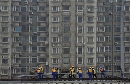 Labourers work on a railway construction project in front of a residential complex in Shenyang, Liaoning province March 5, 2012. REUTERS/Stringer