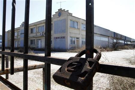 A padlock is seen at the entrance of an abandoned factory in the industrial area at Komotini town in northern Greece March 3, 2012. REUTERS/Grigoris Siamidis