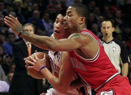 New York Knicks' Jeremy Lin (L) is defended by Chicago Bulls' Derrick Rose during their NBA basketball game in Chicago, March 12, 2012. REUTERS/Jim Young