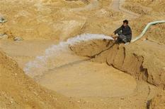 A labourer hoses water into the site of a rare earth metals mine at Nancheng county, Jiangxi province December 21, 2010. REUTERS/Stringer