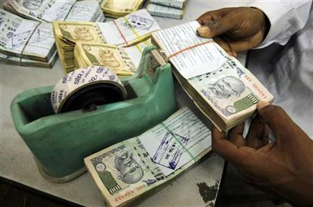 An employee arranges Indian currency notes at a cash counter inside a bank in Agartala February 18, 2010. REUTERS/Jayanta Dey/Files