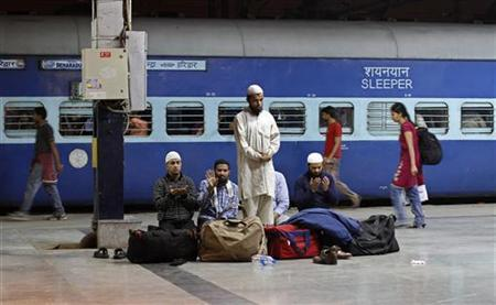 Passengers offer prayers before boarding a train at a railway station in New Delhi March 13, 2012. REUTERS/Adnan Abidi