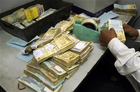 An employee arranges Indian currency notes at a cash counter inside a bank in Agartala, January 29, 2010. REUTERS/Jayanta Dey/Files