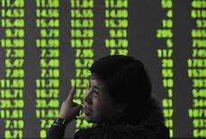 An investor gestures as she talks to another investor (not pictured) in front of an electronic board showing stock information at a brokerage house in Shenyang, Liaoning province March 14, 2012. China shares sank 2.6 percent on Wednesday, the biggest one-day percentage fall in three-and-half months, after Premier Wen Jiabao doused expectations of any near-term easing of measures in the property sector, warning that letting up on regulation would risk chaos in the housing market. REUTERS/Sheng Li