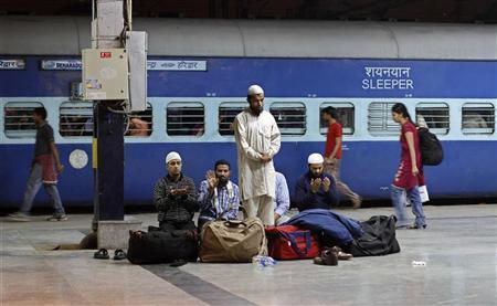 Passengers offer prayers before boarding a train at a railway station in New Delhi March 13, 2012. REUTERS/Adnan Abidi/Files