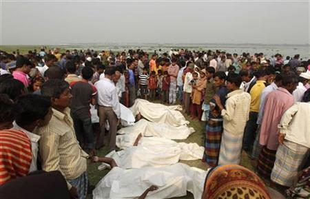 People look for their missing relatives, as bodies are lined up near the site of a ferry accident on Meghna River in Munshiganj district, about 50 km (31 miles) south of Dhaka March 13, 2012. REUTERS/Andrew Biraj