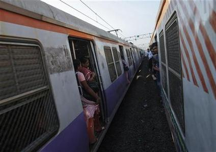 Passengers ride at the open doorways of commuter trains during the morning rush hour in Mumbai March 14, 2012. REUTERS/Vivek Prakash