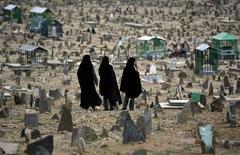 Афганские женщины на кладбище в Кабуле 11 июня 2009 года. Если силы НАТО убьют в Афганистане члена какой-либо семьи, с денежной точки зрения лучше, если военные будут из Германии или Италии, чем из США или Великобритании. REUTERS/Ahmad Masood