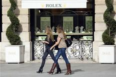 Women walk past a window display of luxury goods maker Rolex in Paris' Place Vendome October 13, 2008. REUTERS/Charles Platiau