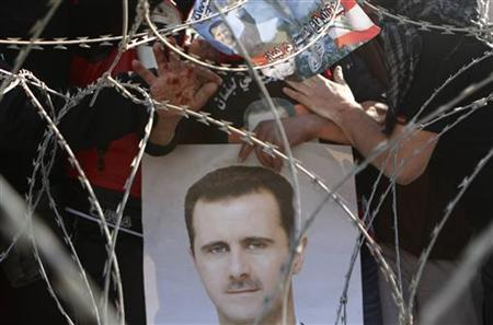 A Syrian living in Lebanon gestures with a bloodied hand above a portrait of Syrian President Bashar al-Assad during a demonstration in support of Assad, in downtown Beirut March 4, 2012.REUTERS/Jamal Saidi