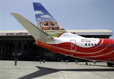 Journalists look at a new Boeing 737-800 aircraft in the livery of Air India Express at Mumbai airport May 24, 2007. REUTERS/Punit Paranjpe/Files