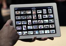 Convidado confere aplicativo de fotos do novo iPad na sala de demonstração após evento de lançamento da Apple, em São Francisco.  A Apple está registrando pré-encomendas recordes para a nova versão do iPad, e o tempo de espera para o envio do tablet agora está entre duas e três semanas.  07/03/2012  REUTERS/Robert Galbraith