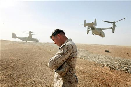 Maj. Matt O'Donnell of Glenelg, MD shields himself from rotor wash as Ospreys carrying the delegation of U.S. Defense Secretary Leon Panetta leave at Forward Operating Base Shukvani, Afghanistan March 14, 2012. REUTERS/Scott Olson/Pool