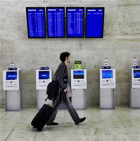 A passenger walks past computerized check-in terminals in the JetBlue terminal at JFK airport in New York November 21, 2007, a day before the Thanksgiving holiday. REUTERS/Jacob Silberberg