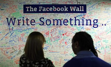 People look at the Facebook wall at their office in New York December 2, 2011. REUTERS/Eduardo Munoz