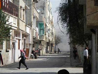 People run for cover from smoke after a shelling in the Karm al-Zeitoun area in Homs, March 12, 2012. Picture taken March 12, 2012. REUTERS/Handout