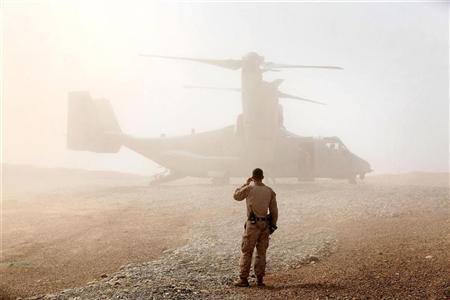 A U.S. Marine watches as an Osprey carrying U.S. Defense Secretary Leon Panetta arrives at Forward Operating Base Shukvani, Afghanistan March 14, 2012. REUTERS/Scott Olson/Pool