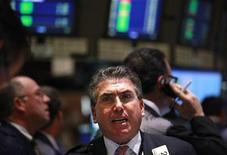 Трейдеры на Нью-Йоркской фондовой бирже 14 марта 2012 года. Уолл-стрит прервала в среду пятидневный период роста, отправившего акции к 4-летним максимумам, так как инвесторы не нашли веских причин к покупкам, хотя бумаги компании Apple Inc и подорожали на 3,8 процента. REUTERS/Brendan McDermid