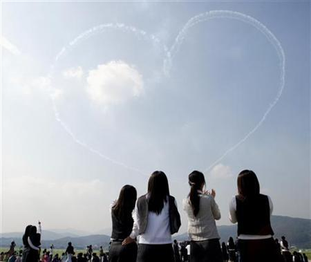 Students watch as the Black Eagles, South Korea's Air Force special flight team, perform during Seoul Air Show 2005 media day at the Seoul Military Airport, south of central Seoul October 17, 2005. REUTERS/You Sung-Ho
