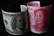 Банкноты в 100 долларов (слева) и 100 юаней в Пекине, 7 ноября 2010 года. Прямые иностранные инвестиции (FDI) в Китай сократились в феврале в годовом исчислении четвертый раз подряд, дополнительно указывая на то, что Народный банк Китая может принять меры для поддержания стабильного роста денежной массы. REUTERS/Petar Kujundzic