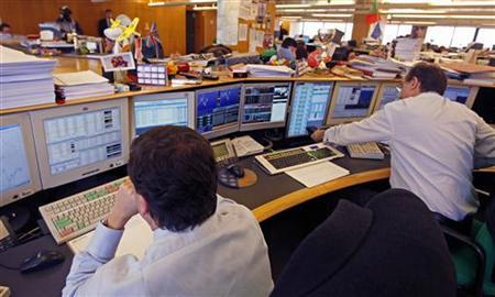 Traders work at a bank market room in Lisbon February 15, 2012. REUTERS/Jose Manuel Ribeiro/Files