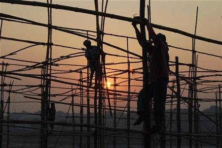 Labourers erect a temporary shelter for Hindu devotees ahead of Magh Mela festival in Allahabad December 1, 2008. REUTERS/Jitendra Prakash/Files