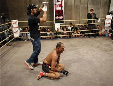 A referee stops a fight as he stands near Amjad Khan, a 30-year-old mixed martial arts fighter, who fell down during the bout at a fight night in Mumbai February 25, 2012. REUTERS/Danish Siddiqui